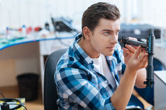 Serious man discovering one of drones parts. Look at this thing. Serious young handsome man discovering one of drones parts attentively while working and stock photo