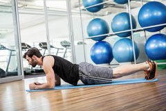 Serious man doing exercise on the mat Stock Photo