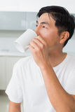 Serious man drinking coffee as he looks away in kitchen Stock Images