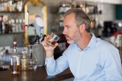 Serious man drinking whiskey at bar counter Stock Photos