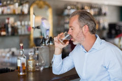 Serious man drinking whiskey at bar counter. In restaurant Stock Photo