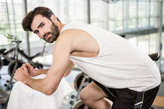 Serious man on exercise bike looking at the camera Royalty Free Stock Photography