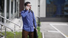 A serious man expects a business of a pertner who is delayed, at this time he speaks on his mobile phone in the street. A serious middle-aged man is talking on a stock footage