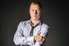 Serious man with folded hands in unbuttoned shirt looking to camera. Serious man looks to camera and holding his jacket. Studio shot flare at background. After royalty free stock photos
