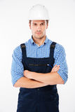 Serious man foreman in hard hat standing with handsom folded. Serious young man foreman in hard hat standing with handsom folded Stock Image