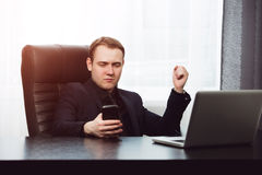 Serious man in formal clother browsin the web with  phone Royalty Free Stock Images