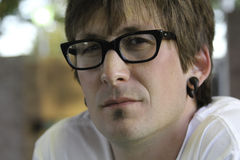 Serious Man with Glasses. Attractive and serious man with black glasses and earrings Stock Photography