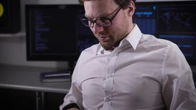 Serious man with glasses, dressed in a white shirt sitting of the working area and prints a report on his laptop. The stock video