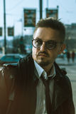 Serious man in glasses and leather jacket looking away outdoors Stock Photo