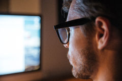 Serious man in glasses using computer and looking at screen Stock Photography