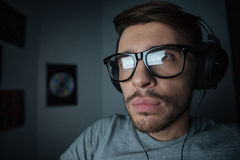 Serious man in glasses using headphones and looking at screen Royalty Free Stock Image