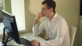 Serious man in glasses works at the computer. Fhd stock footage