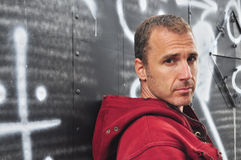 Serious man by graffiti wall. Rugged attractive Caucasian man in red hooded sweatshirt leaning against a graffiti covered wall Royalty Free Stock Images