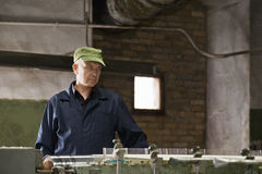 Serious man in green cap at machine Stock Photo