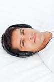Serious man with headphones on lying on his bed Royalty Free Stock Photos