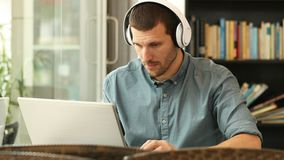 Serious man with headphones using a laptop. Sitting in a coffee shop or library stock video footage
