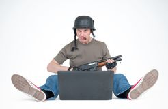 Serious man in helmet with shotgun and cigar, sitting on the floor front of laptop. Armchair warriors games concept Royalty Free Stock Photo