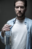 Serious man holding beverage in right hand Royalty Free Stock Images