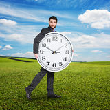 Serious man holding big clock Stock Photo
