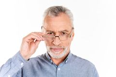Serious man holding his glasses and looking camera isolated. Serious mature bearded man in blue shirt holding his glasses and looking camera isolated over white royalty free stock images