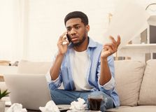 Serious man holding paper and talking on mobile phone. Bad news, bankruptcy. Sad african american man holding paper and talking on mobile phone, working at home stock image