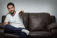 Serious man holding remote control and watching TV Royalty Free Stock Image