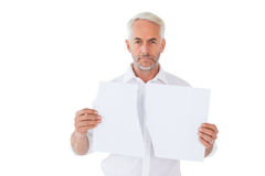 Serious man holding torn sheet of paper Stock Photos
