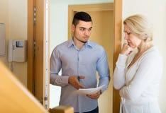 Serious man and housewife at the door Stock Photos