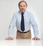 Serious man leaning on a desk Stock Images