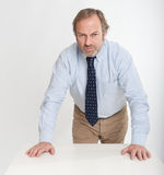 Serious man leaning on a table Royalty Free Stock Photography