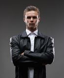 Serious man in a leather coat. A man in a leather coat in the studio Stock Photo