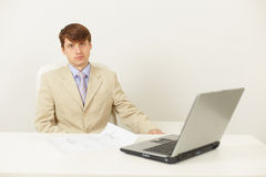 Serious man in light jacket sits at a table Royalty Free Stock Photos