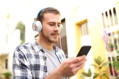 Serious man listening to music on phone walking in the street royalty free stock photography