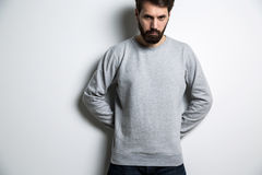 Serious man long sleeves. Serious man in long sleeved sweatshirt on light grey background royalty free stock photos