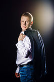 Serious man looks to camera and holding his jacket. Studio shot flare at background. Serious man looks to camera and holding his jacket. Studio shot flare at royalty free stock photos
