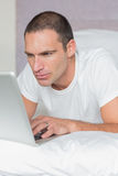 Serious man lying on bed using his laptop Royalty Free Stock Photography