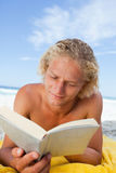 Serious man lying on his beach towel Royalty Free Stock Photos