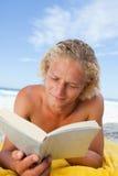 Serious man lying on his beach towel Royalty Free Stock Photos