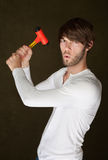Serious Man with Mallet. Serious young Caucasian man raises a mallet Royalty Free Stock Photos