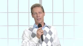 Serious man with microphone talking on blurred background. Business trainer holding microphone and talking to audience, window background stock footage