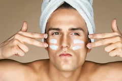 Serious man with moisturizer on the face. royalty free stock photography