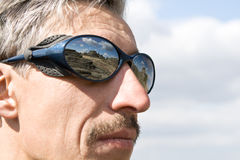 The serious man in mountain points with reflection Stock Image