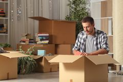 Serious man moving home unboxing belongings in the night stock photo