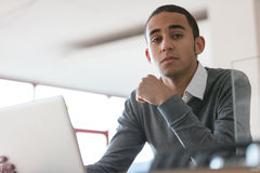 Serious man in office with laptop. Low angle of serious young black man in gray sweater sitting in office with laptop and looking at camera thoughtfully. Copy Stock Images