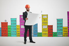 Serious man in orange hardhat with blueprint. Over many-coloured drawing cityscape Stock Photo