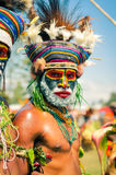 Serious man in Papua New Guinea. Hagen show, Papua New Guinea - circa August 2015: Half-naked man with colour on his face wears colourful knitted cap with Royalty Free Stock Photos
