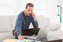 Serious man paying his bills on laptop Royalty Free Stock Photo