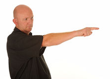 Serious man pointing. Half body portrait of bald middle aged man pointing with finger, white background Royalty Free Stock Images