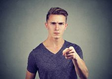 Serious man pointing in accuse. Young casual man pointing at camera with feelings of anger and accusation Royalty Free Stock Photography