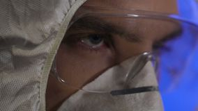 Serious man putting on protective uniform and goggles, nuclear disaster threat stock video